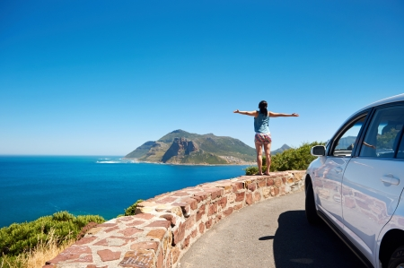 carefree tourist stands on chapmans peak drive with arms outstretched in freedom girl pose with rental car Foto de archivo