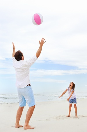 Father and daughter playing on the beach together having fun with beachball  photo