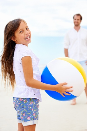 child ball: Father and daughter playing on the beach together having fun with beachball