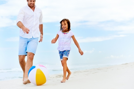 happy healthy family father and daughter running on the beach with ball having fun together photo