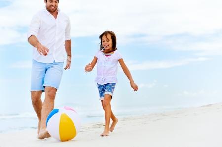 familia saludable: padre feliz familia sana y una hija que se ejecuta en la playa con la pelota se divierten juntos