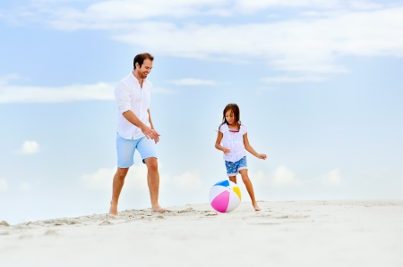 beach ball girl: happy healthy family father and daughter running on the beach with ball having fun together