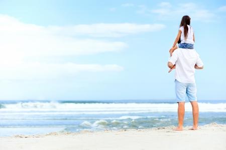 padre e hija: amoroso padre con la hija en los hombros caminando en la playa despreocupada y feliz