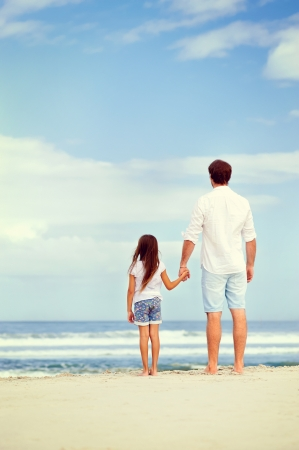 loving hands: Father and daughter holding hands on the beach together happy and loving vacation