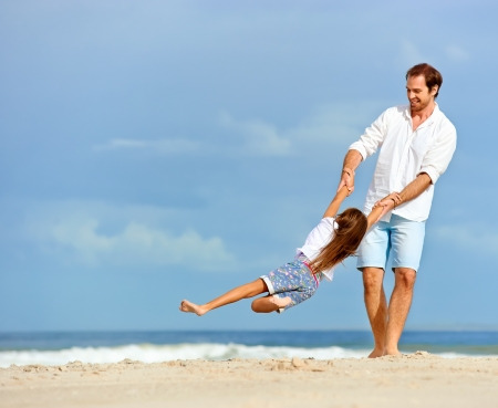 Healthy father and daughter playing together at the beach carefree happy fun smiling lifestyle photo