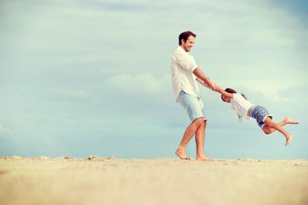 ライフスタイル: 健康的な父と娘のビーチ屈託のない幸せな楽しいライフ スタイルを笑顔で一緒に演奏