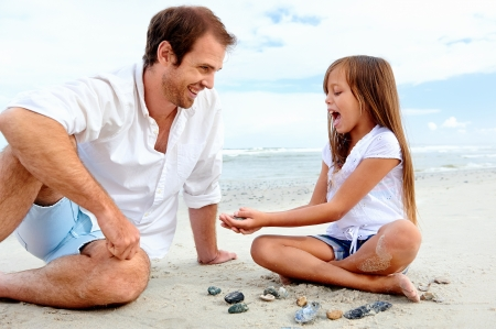 affection: Father and daughter day at the beach collecting shells together having fun and smiling Stock Photo