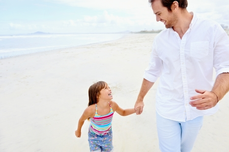 Father and daughter holding hands on the beach together happy and loving vacation photo