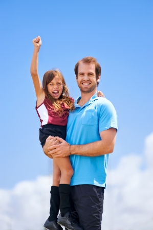 girl kick: soccer dad and daughter practising in the field healthy sporty lifestyle