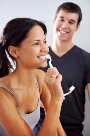 carefree real couple brushing teeth in the bathroom together. daily routine dental health Stock Photo - 18350829