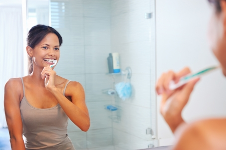 clean teeth: Portrait of attractive woman brushing teeth in bathroom and looking in the mirror at reflection. healthy teeth. Stock Photo
