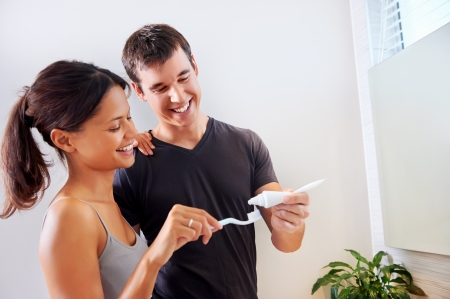 toothpaste: carefree real couple brushing teeth in the bathroom together. daily routine dental health