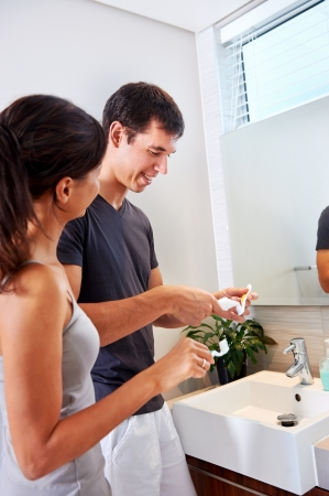 carefree real couple brushing teeth in the bathroom together. daily routine dental health Stock Photo - 18350846