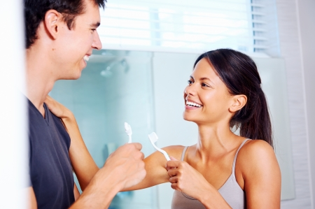 carefree real couple brushing teeth in the bathroom together. daily routine dental health Stock Photo - 18350869