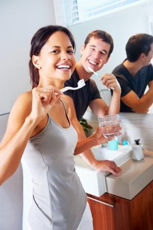 daily routine: pareja real despreocupado cepillarse los dientes en el ba�o juntos. diario de la salud dental de rutina