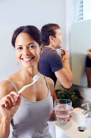 Bathroom routine for happy young couple brushing teeth and shaving in mirror Stock Photo - 18350837