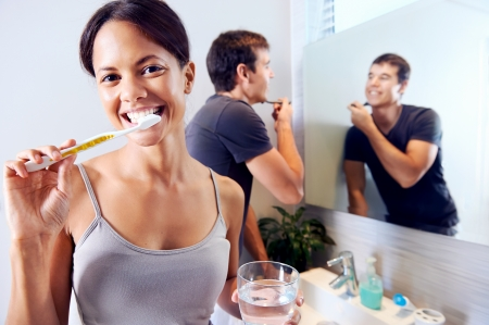 Bathroom routine for happy young couple brushing teeth and shaving in mirror Stock Photo - 18350856