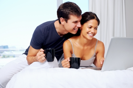 young couple enjoy coffee and relax at home with laptop and love Stock Photo - 18350870