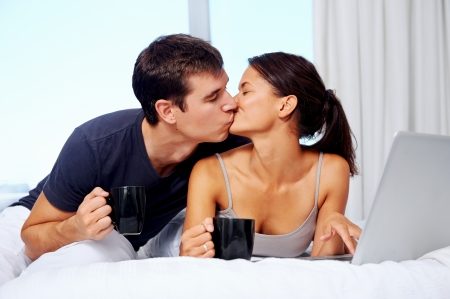 young couple enjoy coffee and relax at home with laptop and love Stock Photo - 18350839
