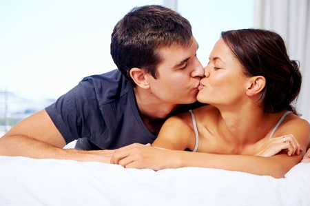kiss couple: adortable multiracial couple kiss on bed at home lifestyle