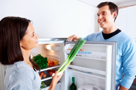 healthy eating couple get fresh vegetables out of the fridge to cook food Stock Photo - 18350843
