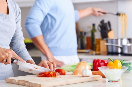 girl with knife: couple cooking healthy food in kitchen lifestyle meal preparation Stock Photo