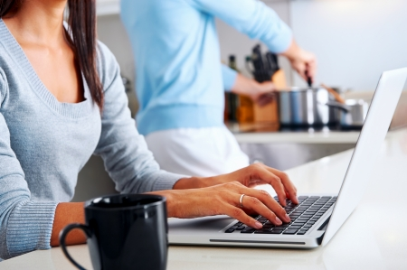 cooking recipe: woman working on laptop in kitchen as boyfriend prepares meal. happy healthy relationship multiracial couple