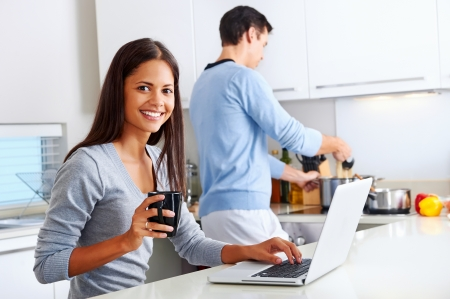 kitchen apron: woman working on laptop in kitchen as boyfriend prepares meal. happy healthy relationship multiracial couple