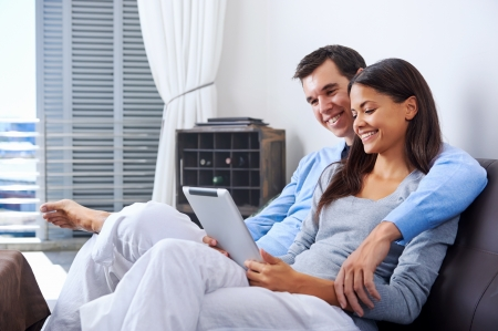 couple relaxing at home with tablet computers reading in the living room on the sofa couch. Stock Photo - 18350848