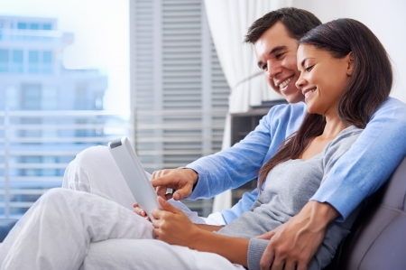 couple relaxing at home with tablet computers reading in the living room on the sofa couch. Stock Photo - 18350877