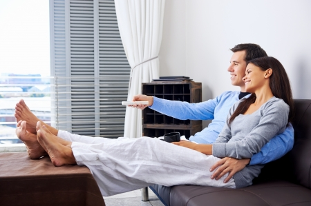 couple reaxing watching tv at home on the couch with embrace and cuddle  Stock Photo