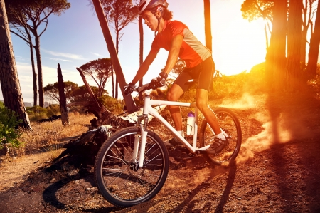 bike race: Mountain Bike cyclist riding single track at sunrise healthy lifestyle active athlete doing sport