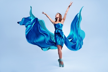 Beautiful ballet dancer with flowing blue fabric dancing with grace in studio photo
