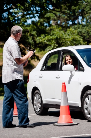 driving school: Learner driver girl with intstructor taking lessons Stock Photo