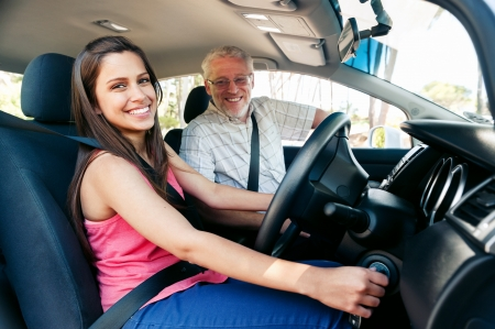 Learner driver girl with intstructor taking lessons photo