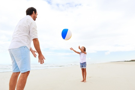 ball of water: Father and daughter playing on the beach together having fun with beachball