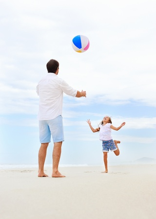 playing in the sea: Father and daughter playing on the beach together having fun with beachball