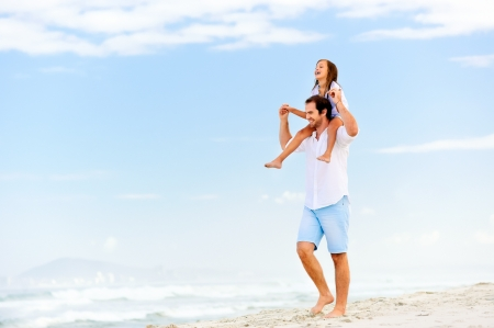 kid's day: loving father with daughter on shoulders walking on the beach carefree and happy