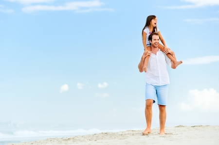 loving father with daughter on shoulders walking on the beach carefree and happy Stock Photo - 18787755