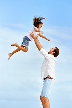 throw: Healthy father and daughter playing together at the beach carefree happy fun smiling lifestyle