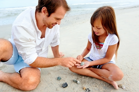 Father and daughter day at the beach collecting shells together having fun and smiling photo