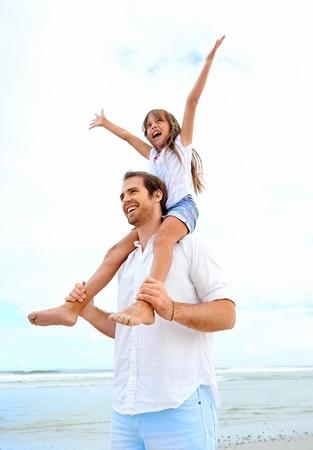 padres: amoroso padre con la hija en los hombros caminando en la playa despreocupada y feliz