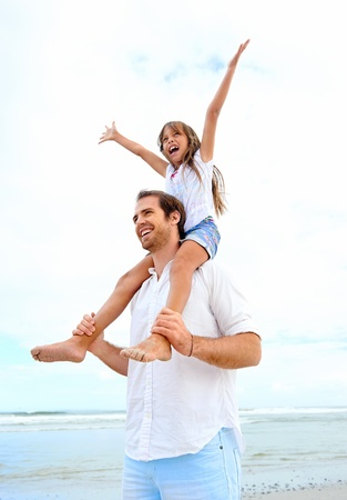 loving father with daughter on shoulders walking on the beach carefree and happy photo