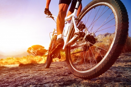 mountain bicycle: low angle view of cyclist riding mountain bike on rocky trail at sunrise