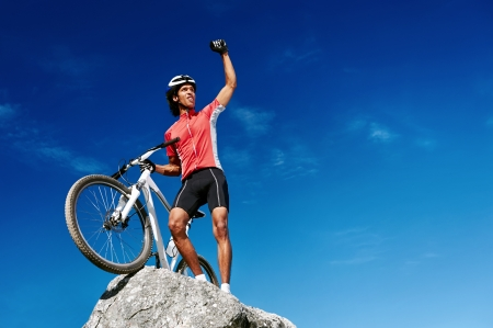 confident mountain bike man celebrating making the top of the peak happy and cheerful Stock Photo - 18911552