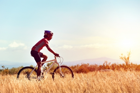 cyclist man riding mountain bike in field horizontal view of healthy lifestyle