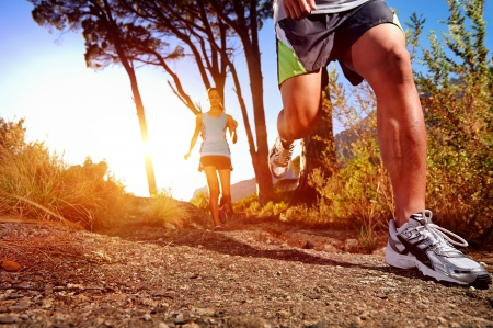 trail: Trail running marathon athlete outdoors sunrise couple training for fitness and healthy lifestyle