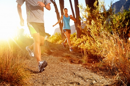 forest trail: Trail running marathon athlete outdoors sunrise couple training for fitness and healthy lifestyle