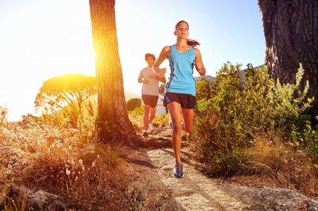 woman running: Trail running marathon athlete outdoors sunrise couple training for fitness and healthy lifestyle