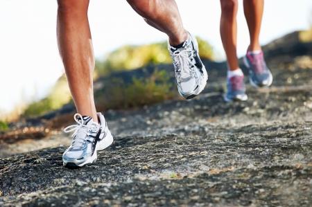 mujeres corriendo: ruta carrera de marat�n pies sobre la aptitud f�sica de rock y estilo de vida saludable Foto de archivo